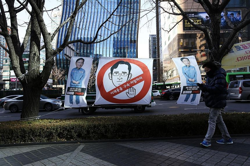 A placard outside the Samsung office features a cartoon in the likeness of Mr Lee Jae Yong. Many Koreans fear that Samsung's troubles would hurt the national economy.