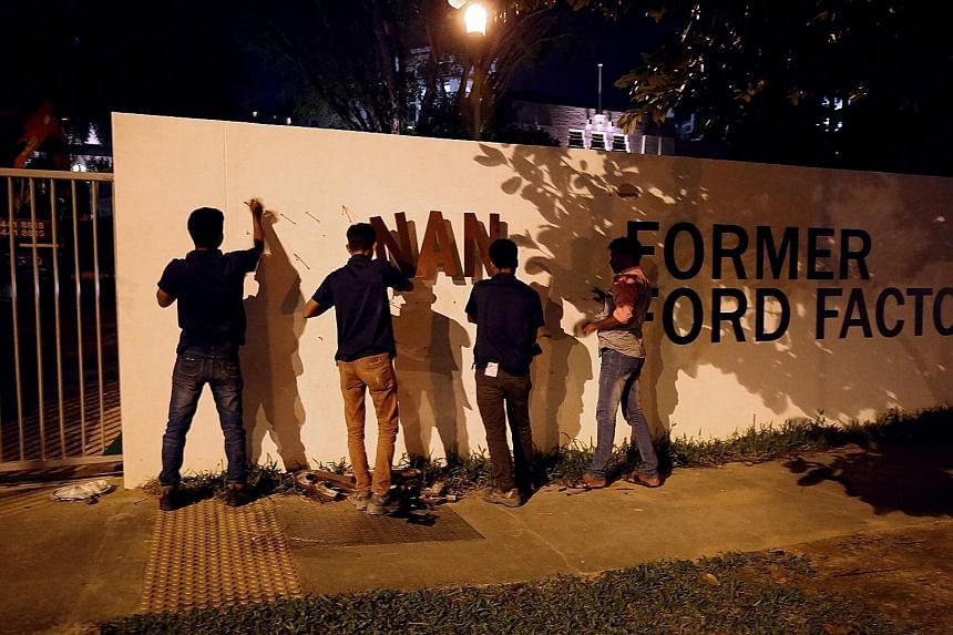 Workers removing the signage for the gallery at the Former Ford Factory in Upper Bukit Timah Road last night. Other signs carrying the old name have also been removed or covered.