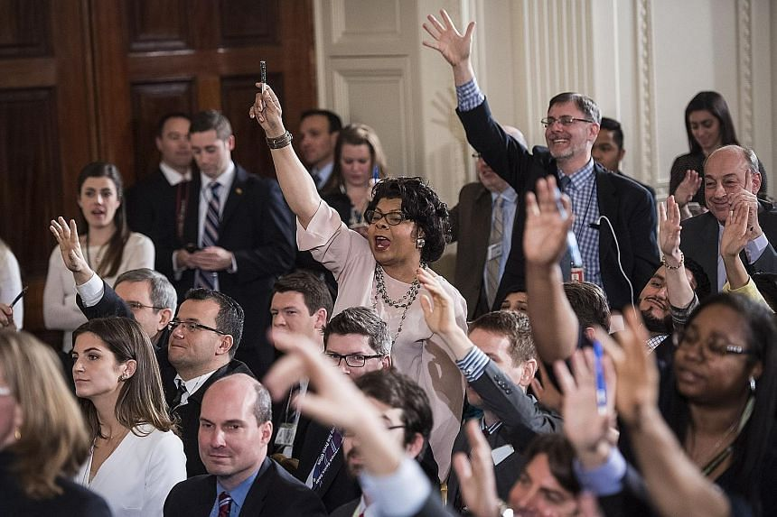 Reporters raising their hands to ask Mr Trump questions during his first solo press conference in the East Room of the White House on Thursday.