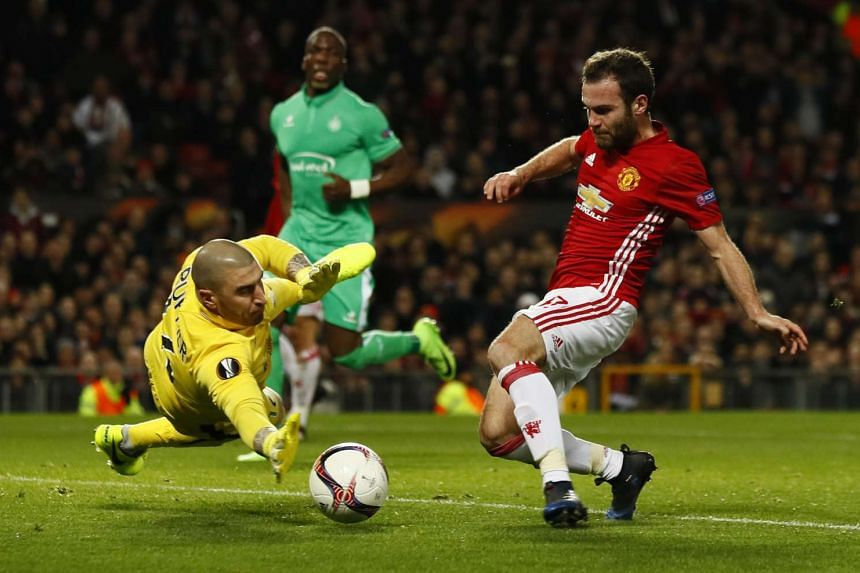 Manchester United's Juan Mata shooting wide under pressure from Saint-Etienne's Stephane Ruffier.