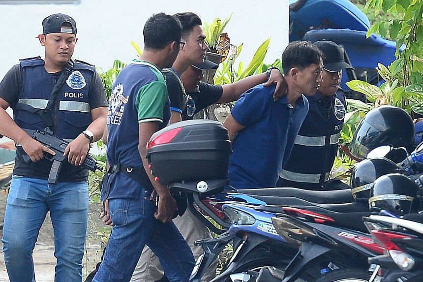 Malaysian police escorting a man identified as Ri Jong Chol (second right) to a police station in Sepang on Feb 18, 2017.