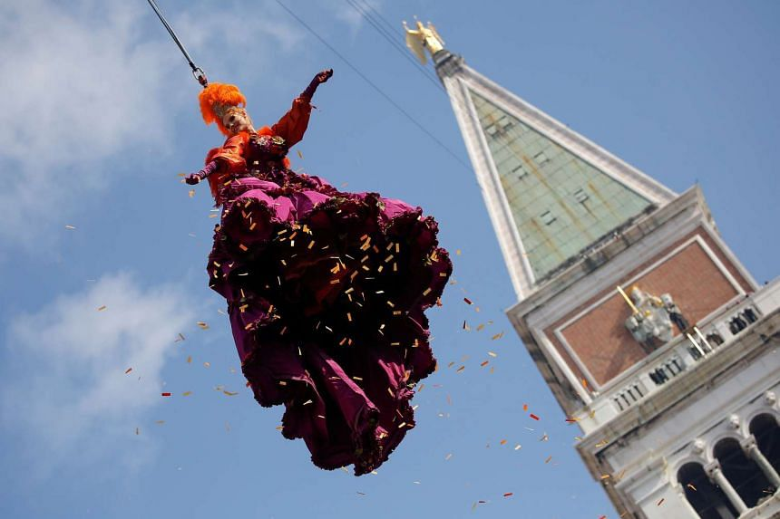 """Ms Claudia Marchiori, dressed as an """"angel"""", descending on St Mark's Square in Venice on Feb 19, 2017."""