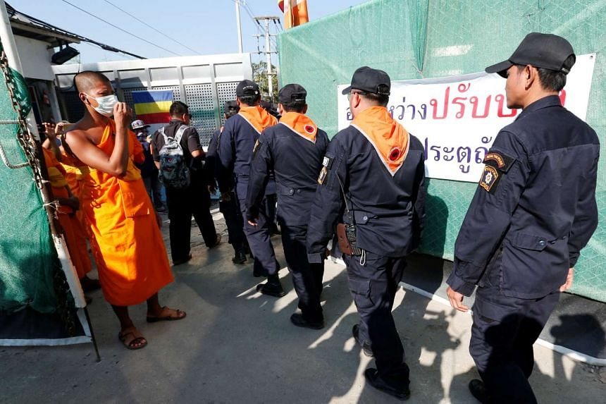 Policemen walking past Buddhist monks at the Dhammakaya Temple to search for former abbot Phra Dhammachayo, in Pathum Thani province on Feb 17, 2017.