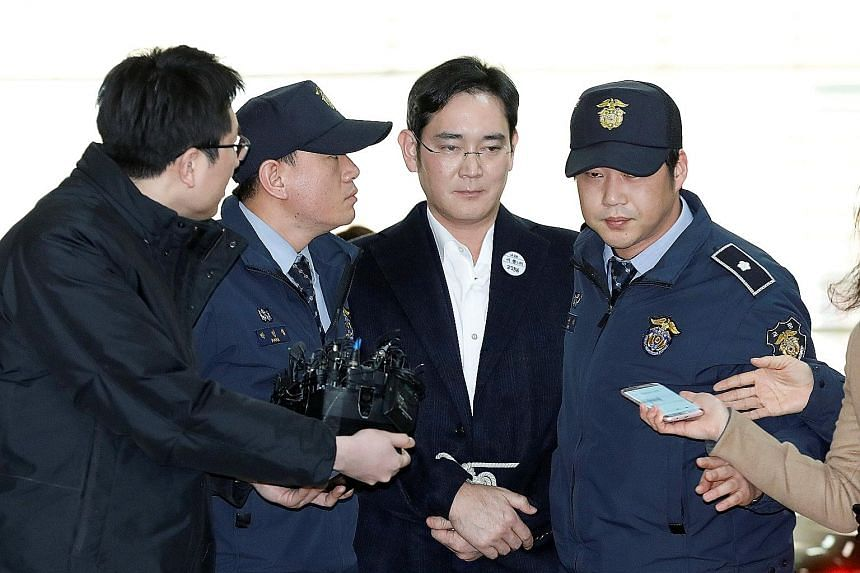 Samsung Group chief Lee arriving at the office of special prosecutors in Seoul yesterday. He was arrested a day earlier for his alleged role in a corruption scandal that has led to the impeachment of South Korean President Park Geun Hye, and he spent