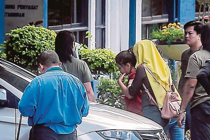 Malaysian police with Siti Aisyah, one of the four suspects arrested in connection with Mr Kim's death. The Indonesian police chief has suggested that she was duped into taking part in the alleged assassination.