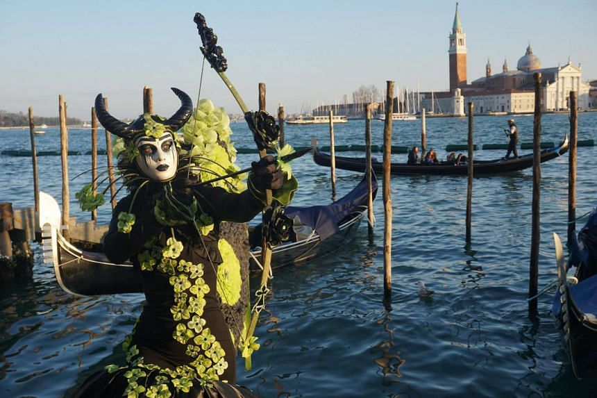 People wearing costumes and masks waiting for the traditional Flight of the Angel that marks the beginning of the Venice Carnival, on Feb 19, 2017.