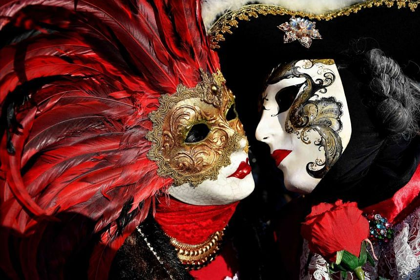 Revellers wearing masks and period costumes pose as they take part in the Venice Carnival on Feb 18, 2017.