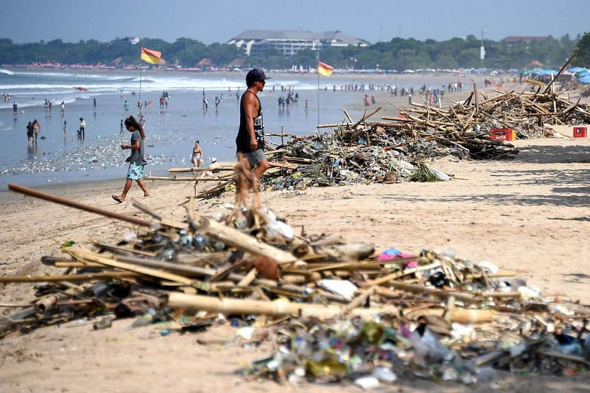 This file photo taken on Dec 19, 2016, shows a tourist walking past debris washed up on Kuta beach near Denpasar on Indonesia's resort island of Bali.