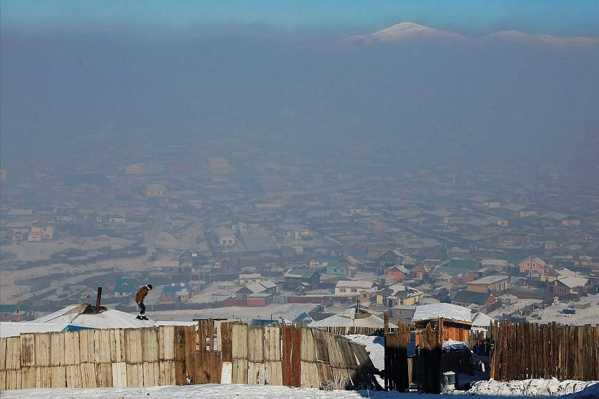 A man walks on the roof of a traditional ger home while fixing the chimney of a coal burning stove on a cold hazy day on the outskirts of Ulaanbaatar, Mongolia on Jan 19, 2017.