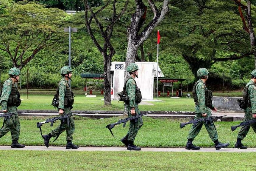 NSmen carrying their weapons for a live firing exercise at Nee Soon Camp.