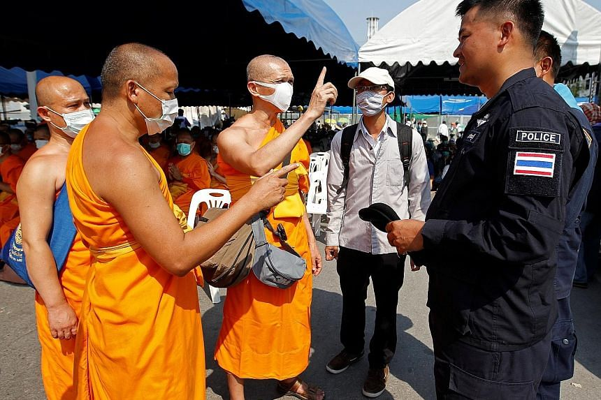Buddhist monks speaking with policemen at the gate of Dhammakaya Temple yesterday. The temple's former abbot, Phra Dhammachayo, faces charges such as conspiracy to launder money and taking over land illegally.
