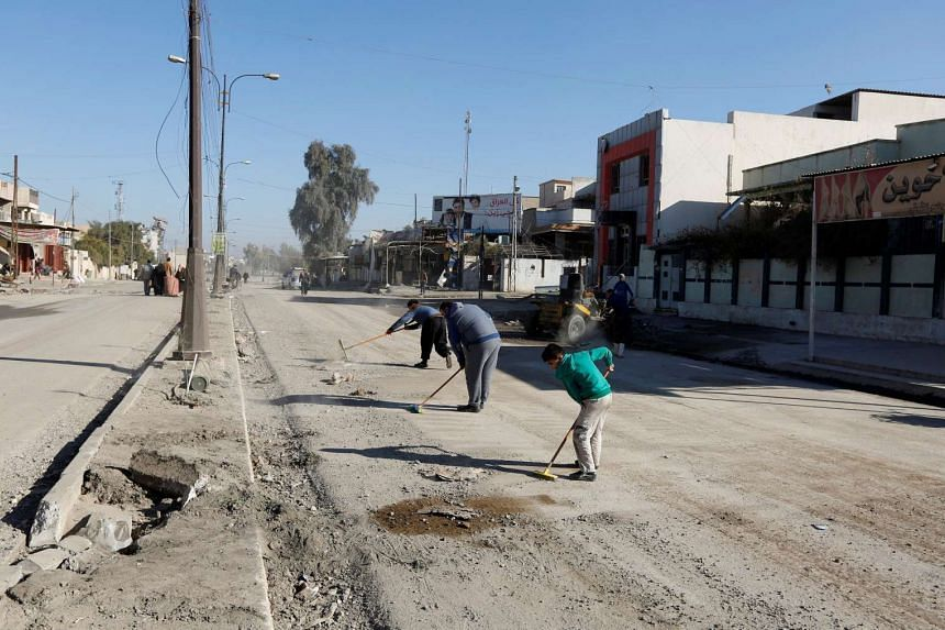 People clean the street after they return to their home in Al-Zuhoor neighborhood of Mosul, Iraq, on Jan 12, 2017.