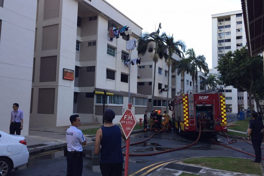 Residents gather outside the cordon area, where a fire broke out in a unit at Blk 138 Bedok Reservoir Road.