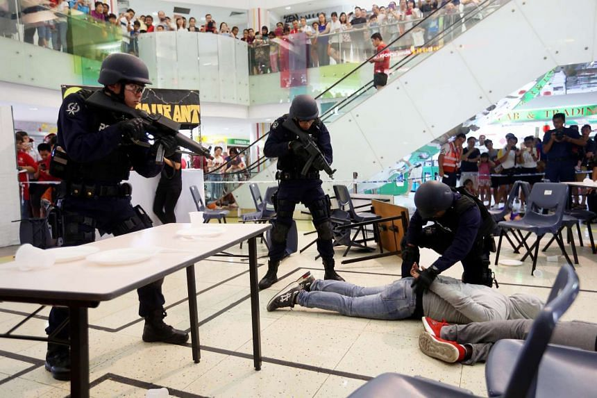 """Officers from the Emergency Response Team taking control of Gek Poh Shopping Centre after it was """"attacked""""."""