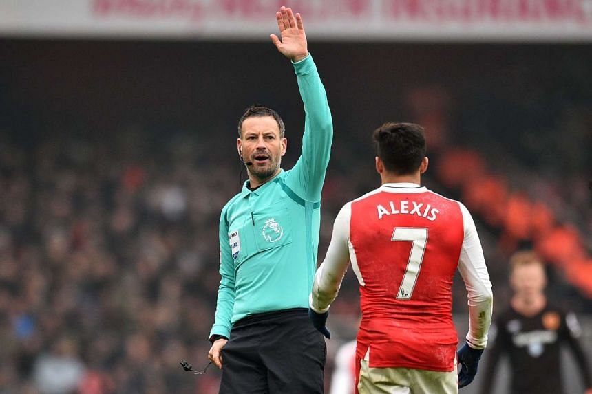 English referee Mark Clattenburg (left) gestures to Arsenal's Chilean striker Alexis Sanchez during the English Premier League football match at the Emirates Stadium in London on February 11, 2017.