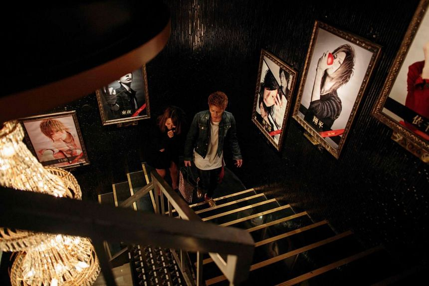 Male host Noel (right) and his customer Megumi Suzuki (left) walk past portraits of male hosts as they leave a host club in the Kabukicho red-light district in Tokyo, after spending some time together drinking and chatting.