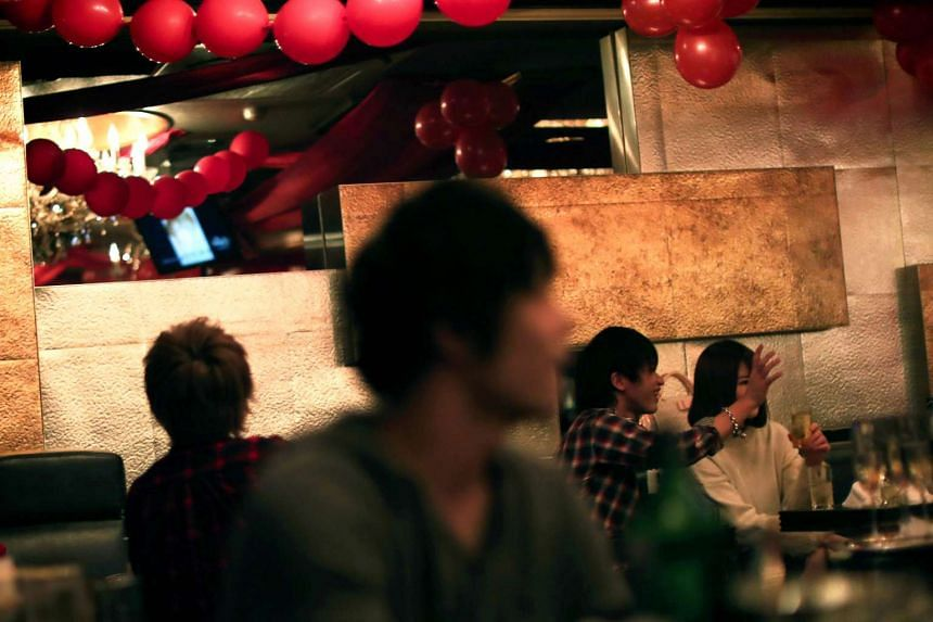 Male hosts accompany women at a host club in the Kabukicho red-light district in Tokyo.