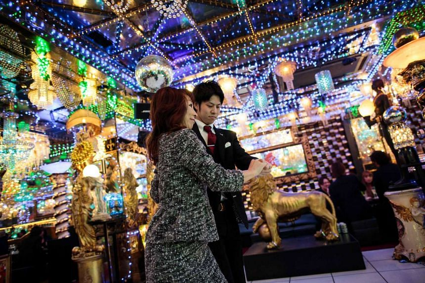 A woman dances with a male host at a host club in the Kabukicho red-light district in Tokyo.