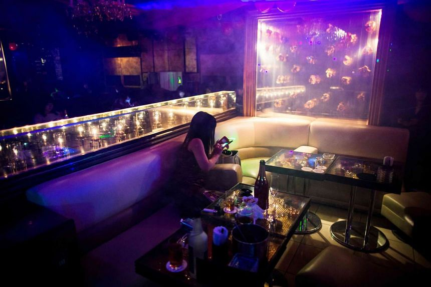 A woman checks her phone as she waits for her host at a host club in the Kabukicho red-light district in Tokyo.
