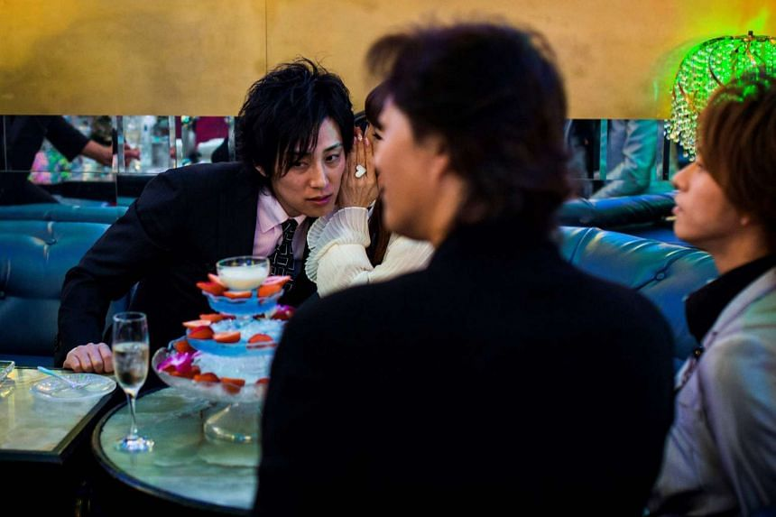 A female customer whispers to her Japanese host Ichi (left), at a host club in the Kabukicho red-light district in Tokyo.
