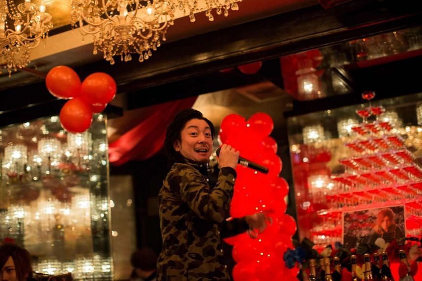 A male host speaks into a microphone during birthday celebrates for a colleague at a host club in the Kabukicho red-light district in Tokyo.