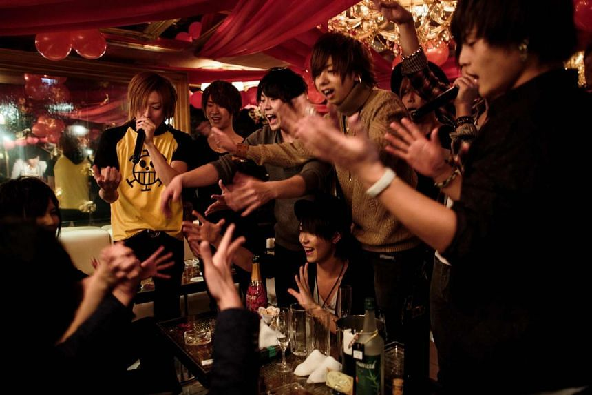 Male hosts cheer to celebrate the birthday of their colleague Haruma (bottom left) at a host club in the Kabukicho red-light district in Tokyo.