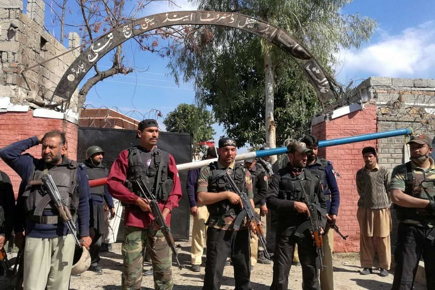 Policemen stand guard after a blast and shooting outside the courthouse in Charsadda.