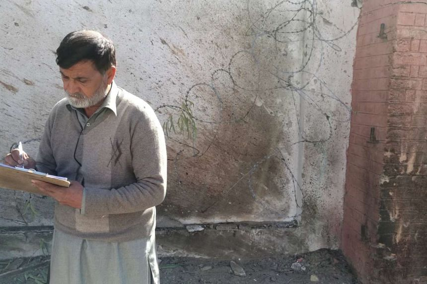An investigator takes notes at a courthouse after an attack by suicide bombers in Charsadda.