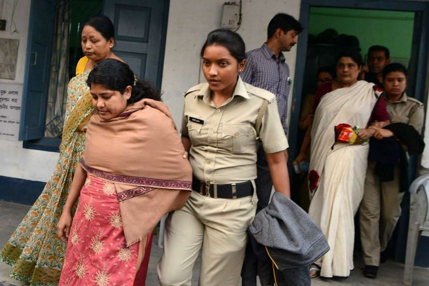 Indian police officials escort Chandana Chakraborty (second right) and Sonali Mondal (second left) from a police station in Jalpaiguri on Feb 21, 2017, for a medical check up after their arrest as part of an alleged child trafficking scandal.