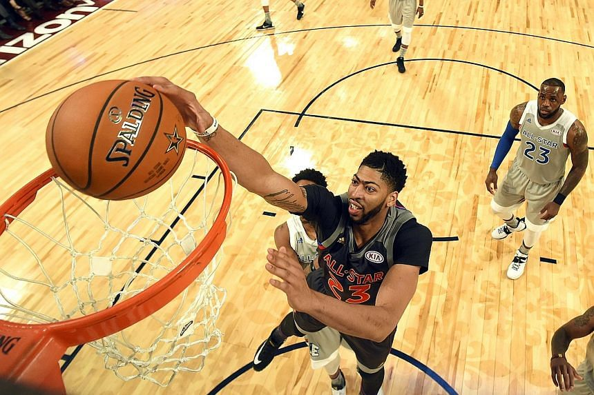 Western Conference forward Anthony Davis slam dunking as Eastern Conference forward LeBron James looks on during the NBA All-Star Game in New Orleans.