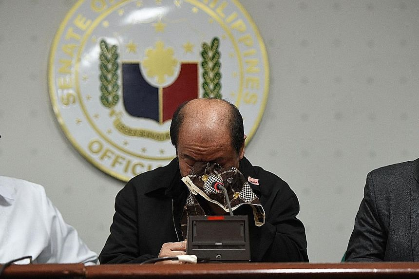 Mr Lascanas wiping his tears yesterday at the news conference as he spoke about crimes allegedly ordered by Mr Duterte.