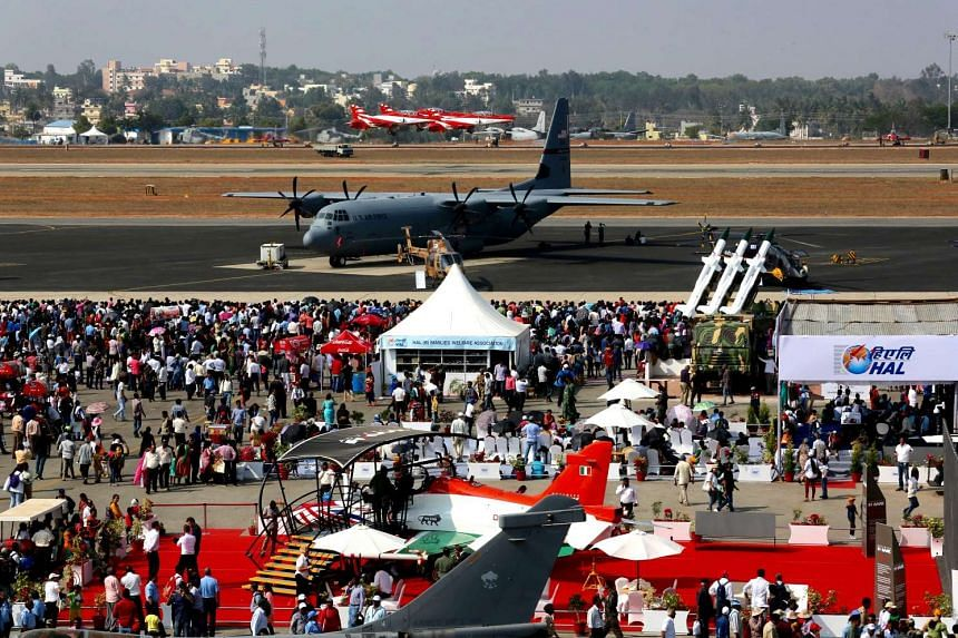 Visitors watching planes of the Indian Air Force Surya Kiran team performing near a US Air Force Super Hercules C130J during the Aero India-2017 in Bangalore, India, on Feb 17, 2017.