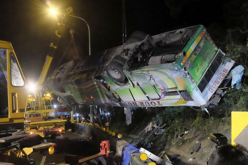 A bus that crashed along a highway is lifted by cranes in Taipei, on Feb 14, 2017.