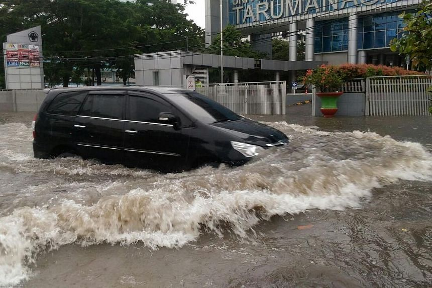 A car trying to navigate through flood water in Grogol, West Jakarta, on Tuesday (Feb 21, 2017) morning. Floods inundated several areas in the outskirts of Indonesia's capital after a heavy downpour. Flood levels at some areas reached as high as 1.5m