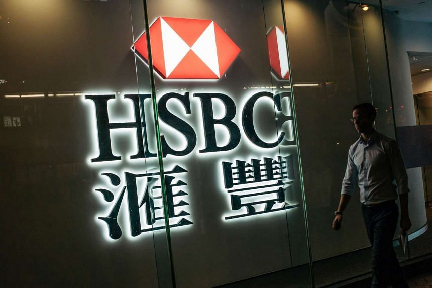 A pedestrian walking past a HSBC signage in the Central district of Hong Kong.