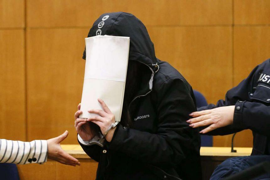 Naree K., another defendant in the exorcism murder case, hides behind a folder.