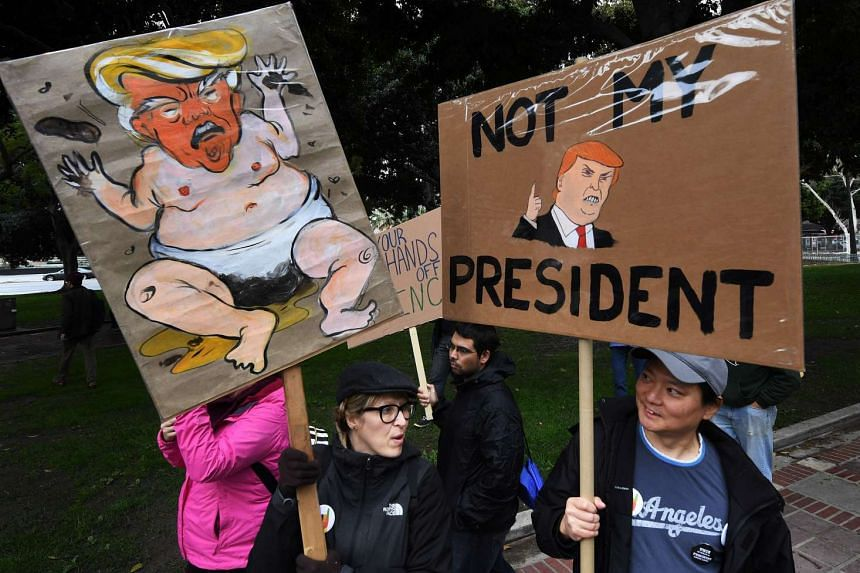 Protesters carry signs at a 'Not My President Day' demonstration in Los Angeles, California, on Monday (Feb 20, 2017).