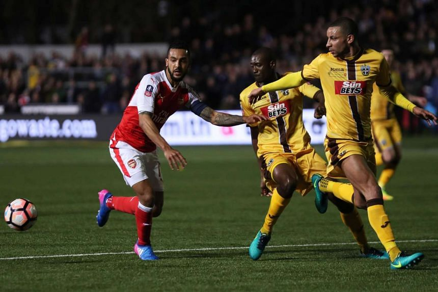 Sutton United's Bedsente Gomis and Craig Eastmond in action with Arsenal's Theo Walcott.