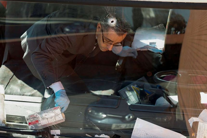 An investigator is seen inside a gas cylinder delivery truck with bullet holes in the windscreen after police fired at it to stop the driver, in Barcelona, Spain, on Feb 21, 2017.