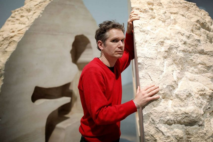 """French artist Abraham Poincheval poses in front of his artwork Pierre (""""Stone"""") in Paris, Feb 2, 2017."""