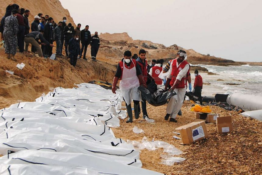 Libyan Red Crescent volunteers recovering the bodies of 74 migrants that washed ashore.