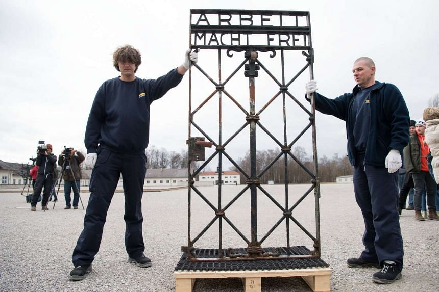 """Workers present the iron gate with the slogan """"Arbeit macht frei"""" after its return, Feb 22, 2017."""