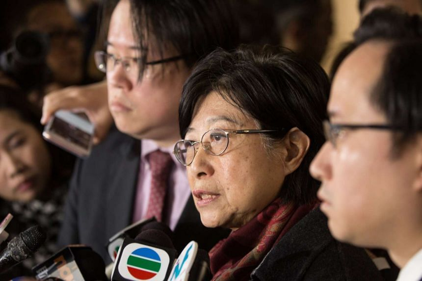 Mrs Selina Tsang (centre), flanked by her sons Thomas (right) and Simon, speaking to the media outside the Hong Kong High Court on Feb 22, 2017.