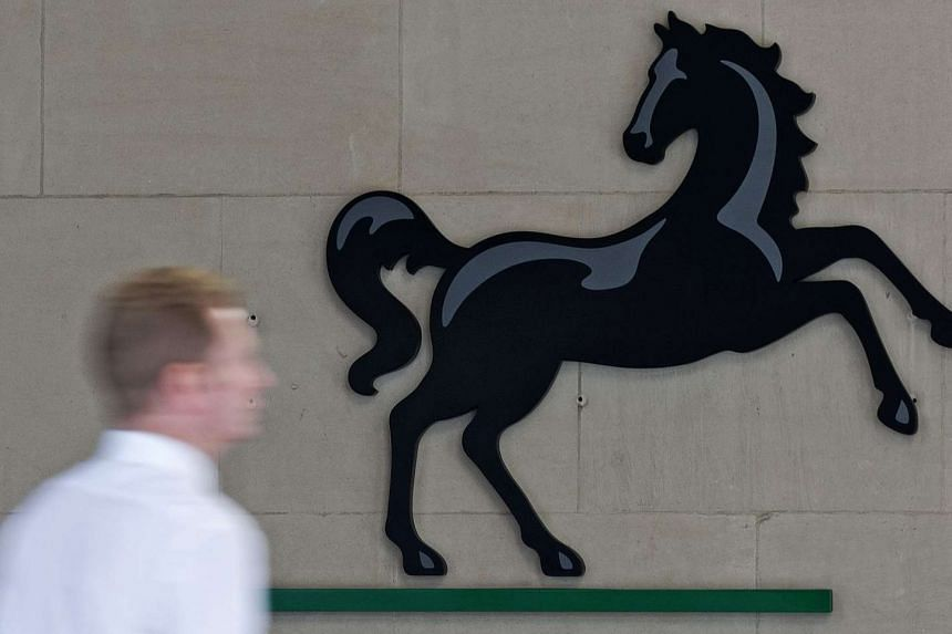 A man passes a Lloyds logo outside the entrance to on office of Lloyds Banking Group in the City of London on July 28, 2016.