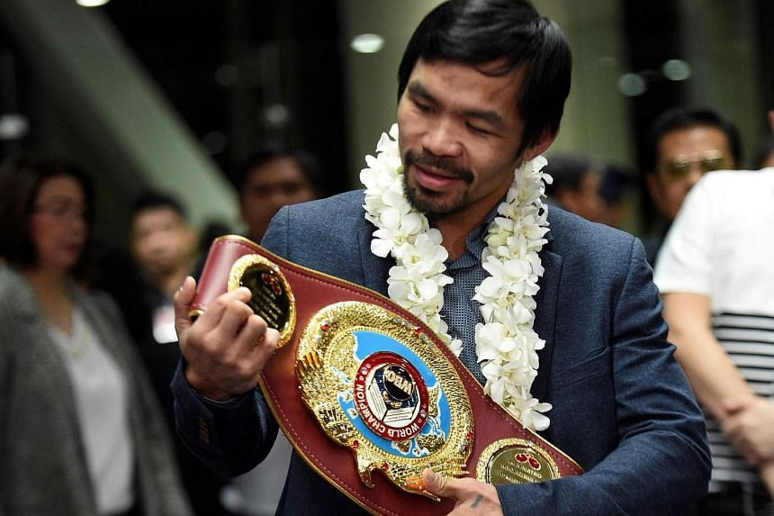 Philippine boxing icon Manny Pacquiao with his welterweight title at the Manila airport on Nov 8, 2016.