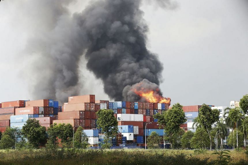 The fire rages on with containers in the foreground.
