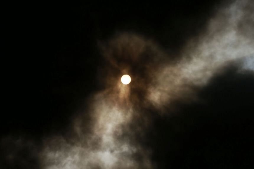 The sun obscured by the thick smoke from the fire.