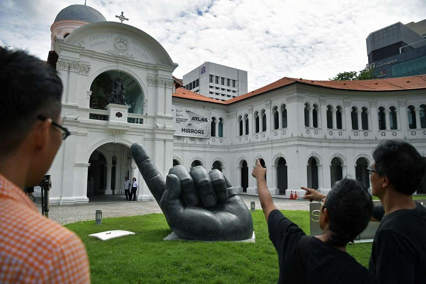 A large hand emerges from the ground. Entitled Inscription Of The Island, the bronze sculpture was lowered onto the front lawn of the Singapore Art Museum on Oct 18, 2016, ahead of the Singapore Biennale.