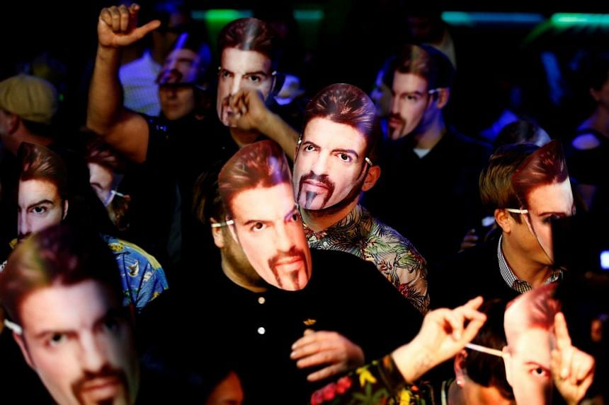 Fans of the late George Michael wear masks at a tribute night event, in London, Jan 6, 2017.