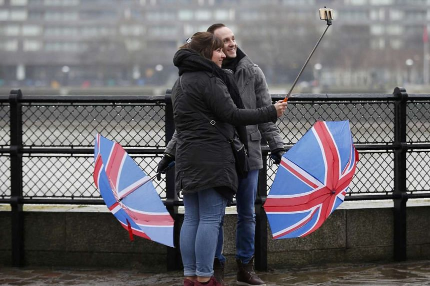 Tourists lower their Union Flag umbrellas as they take a selfie in the rain near Tower Bridge, in London, Jan 15, 2017.
